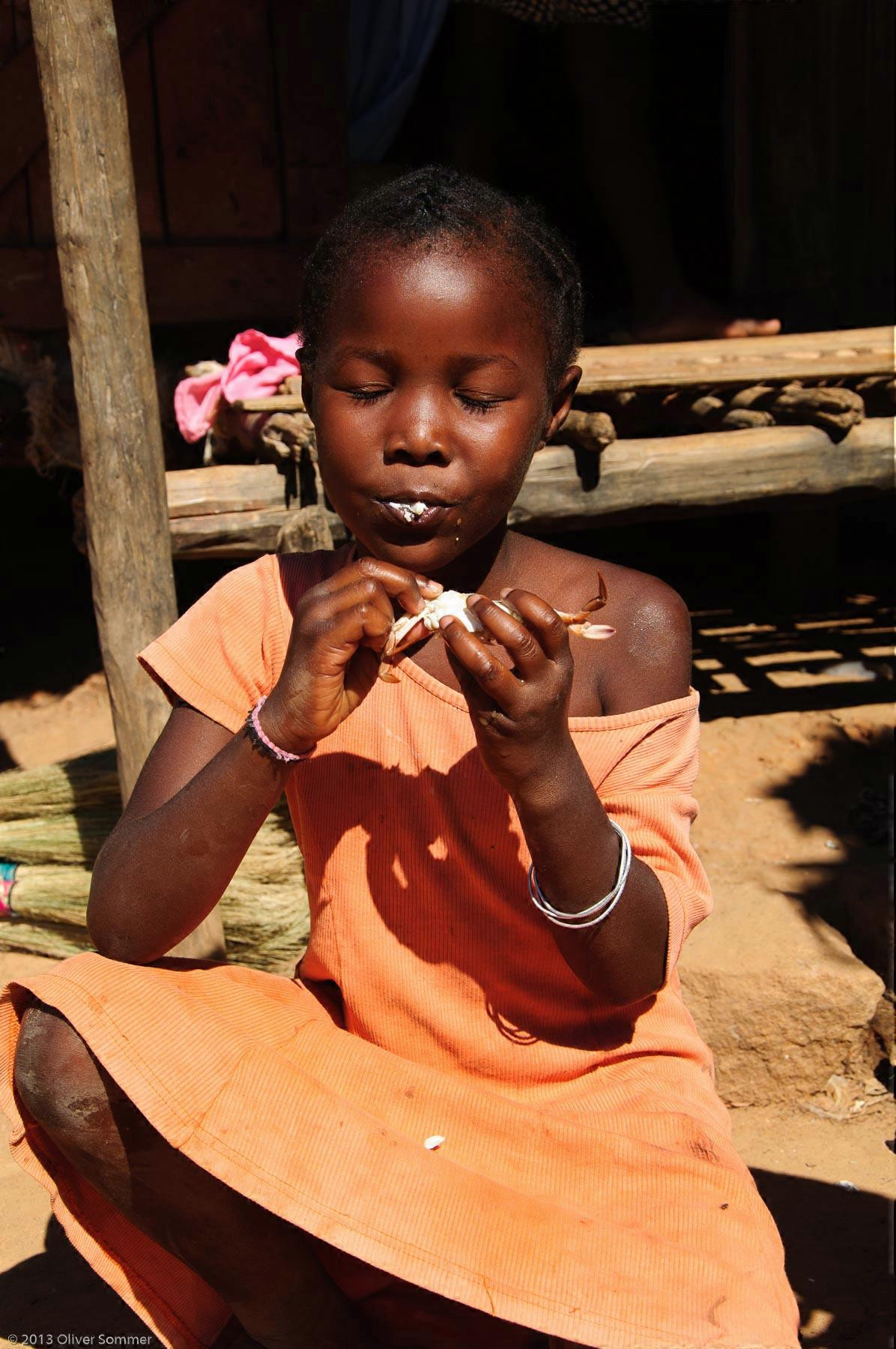 Girl eating Crab Madagascar